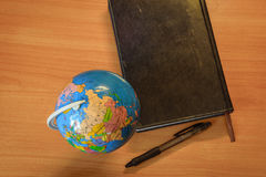 Globe and notebook Stock Image