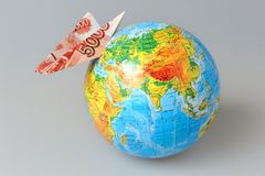 Globe with origami plane made from banknote on gray Royalty Free Stock Photography