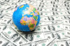 Globe over many dollar bank notes Royalty Free Stock Photography