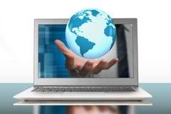 Globe in palm through laptop Stock Photo