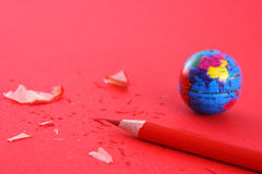 Globe and pencil on red stock photos