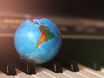 Globe on the piano keys, a small model of the earth stock image