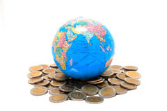 Globe on the pile of coins - isolated Royalty Free Stock Photography