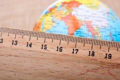 Globe placé près d'une règle en bois Images stock