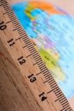 Globe placé près d'une règle en bois Image stock