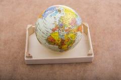 Globe placé sur le fond brun image stock