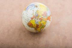 Globe placé sur le fond brun photographie stock