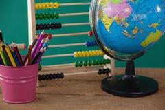 Globe, porte-plume et abaque sur la table en bois Photo libre de droits