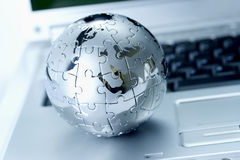 Globe puzzle. Isolated on a laptop Stock Photography