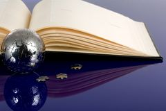 Globe puzzle with book Stock Image