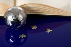 Globe puzzle with book Royalty Free Stock Images