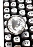 Globe on QWERTY. Crystal globe on old typewriter keyboard Royalty Free Stock Image
