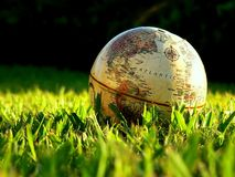 Globe resting in Grass. An antique globe resting in the grass with a long shadow stock photography