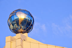 Globe on the roof over sky Royalty Free Stock Image