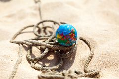 Globe on a rope on the sand. Mini globe lying on a rope on the sand close-up Royalty Free Stock Photos
