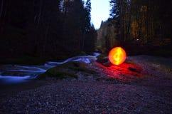 Globe rouge rougeoyant près de l'eau Photos stock