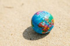 Globe on the sand close up. A small globe lies on the sand lit by the sun royalty free stock images