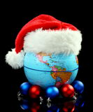 Globe Santa hat and Christmas balls. Royalty Free Stock Photo