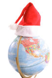 Globe with santa hat vertical upclose. Photo of a globe with santa hat vertical upclose Royalty Free Stock Photography