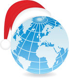 Globe with Santa's hat. Stock Photos
