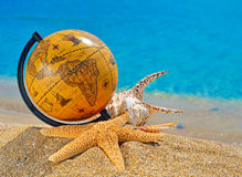 Globe, shells, starfish in the beach near ocean Royalty Free Stock Image