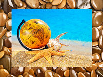 Globe, shells, starfish in the beach near the ocean Stock Images