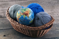 Globe and skeins of yarn in a wicker basket Stock Photography