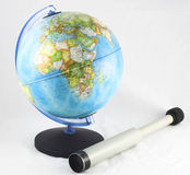 Globe and a spyglass. Pirate and tourism adventure around a globe on a white background Stock Photos