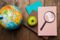 Globe, stack of books and magnifier on wood Royalty Free Stock Photos
