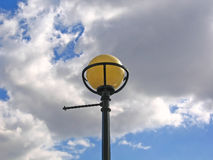 Globe street lamp and sky. Old fashioned globe street lamp against a cloudy blue sky in England stock image