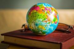 Globe sur la couverture d'un vieux livre Photo stock