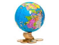 Globe sur pièces de monnaie Photo stock