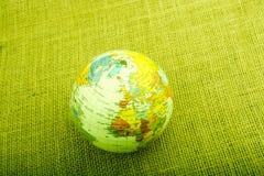 Globe sur un fond brun de tissu Photo stock