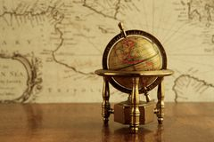 Globe on a table. Globe against map on a wall stock photography