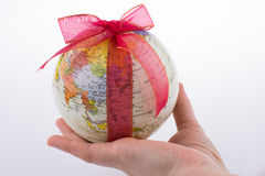 Globe tied with ribbon. Globe tied with red ribbon on a white background Royalty Free Stock Photos