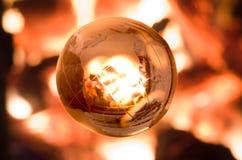 Globe transparent dans le feu Photos stock