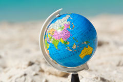 Globe on tropical beach. Travel concept Royalty Free Stock Photography