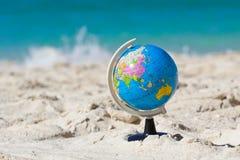 Globe on tropical beach Stock Photos