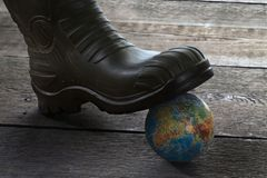 Globe under the foot in a rubber boot Stock Photography