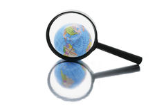 Globe under Magnifying Glass Royalty Free Stock Images