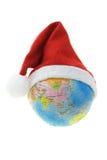 Globe wearing Santa hat Stock Photography