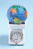 Globe on Weighing Scale royalty free stock photography