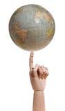Globe on wooden finger Stock Photos