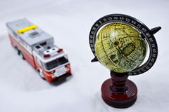 Globe with wooden stand and with fire engine model on white - fire fighting Royalty Free Stock Photos