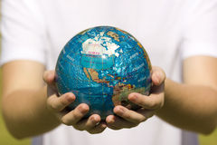Globe in young hands Stock Photo