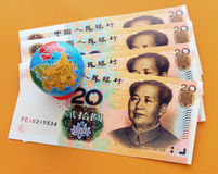 Globe on the yuan. Isolated on yellow background Stock Photos