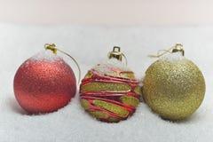 Globes colorés de Noël entourés par la neige Photos stock