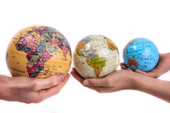 Globes in hand. Two hands holding holding three globes in hand on white background Royalty Free Stock Photography
