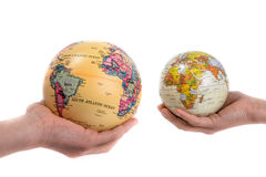 Globes in hand. Two hands holding holding two globes in hand on white background Royalty Free Stock Photo
