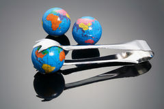 Globes and Tong. With Reflections Stock Photo